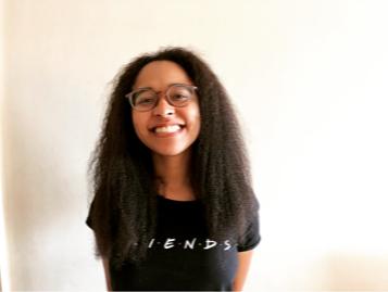 Foto da autora do blog, Gabriela Del Carmen. Ela utiliza uma blusa preta com o logo da série Friends. Usa óculos e aparece sorrindo, com os cabelos abaixo dos ombros.