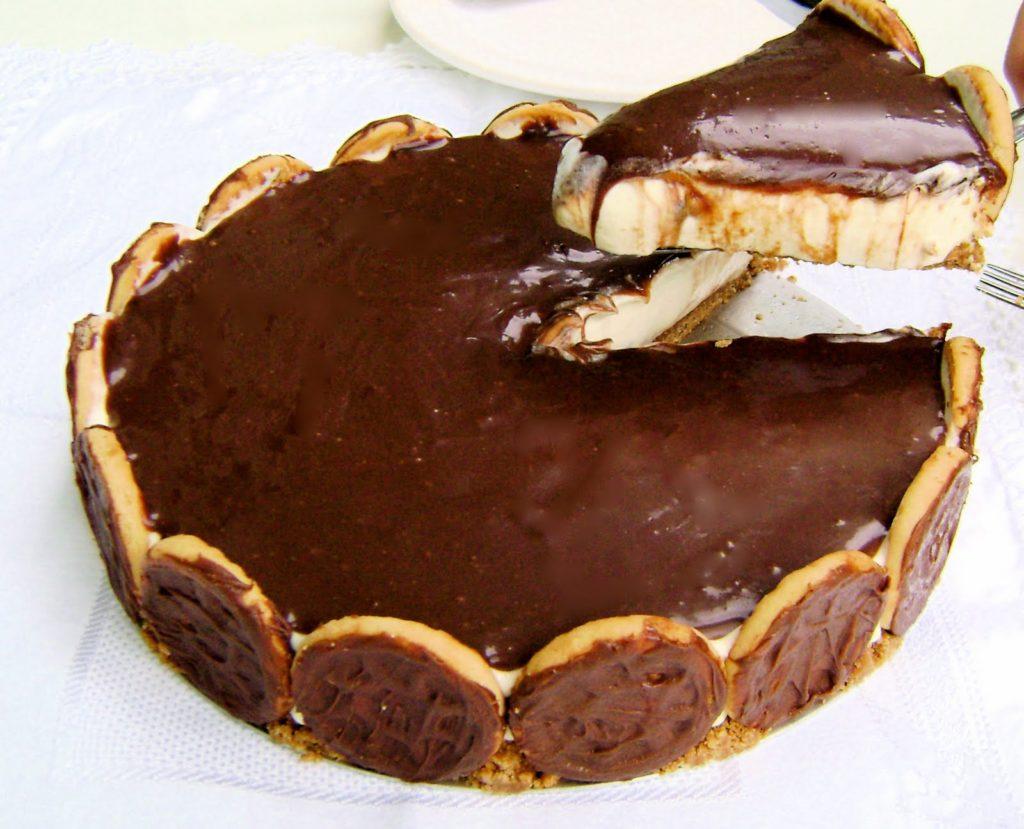 Foto de uma torta holandesa, com um pedaço cortado. A sobremesa está decorada com bolacha, tem uma cobertura de chocolate e recheio de creme.