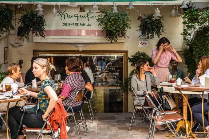 Fachada do restaurante Muquito, cozinha de família. Na foto, tirada por Ricardo D'Angelo/Veja SP, diversas mulheres, de diferentes idades, estão sentadas nas mesas aproveitando a refeição.