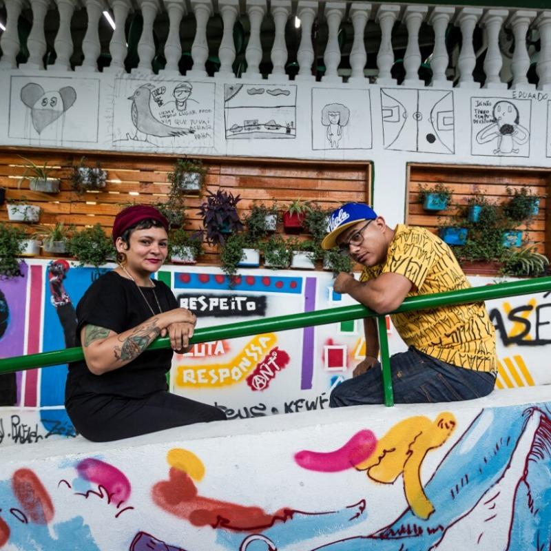 Na foto, Adélia Rodrigues e Edson Leite, sócios do projeto Gastronomia Periférica, aparecem sentados em uma rampa, apoiados no corrimão. Foto: Leidyla Nascimento