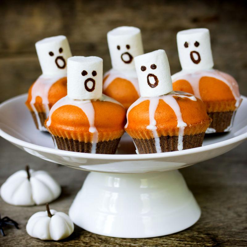 Muffins assombrados laranjas, com pequenos fantasmas em cima para o Halloween. Foto: Divulgação/Vigilantes do Peso